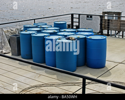 blue oil fuel barrels on a wooden dock by the river, water in background and area is surrounded by a rail railing - Stock Photo