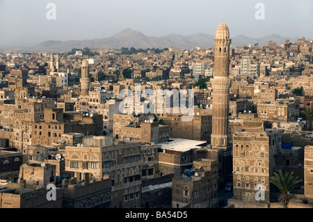 A minaret and traditional tower houses on the skyline of the old city of Sana'a, Yemen. - Stock Photo