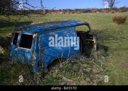 old blue rusted abandoned wreck of an old mini van in a field in county armagh northern ireland uk - Stock Photo