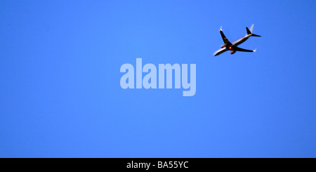 Jet airliner gliding thru a brilliant blue sky in a panoramic crop - Stock Photo