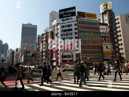 Pedestrians cross the road in Shinjuku, Tokyo, Japan, Asia - Stock Photo