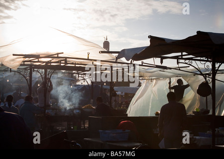 Food stalls on the Jemaa el Fna seen in silhouette against the setting sun in Marrakech, Morocco - Stock Photo