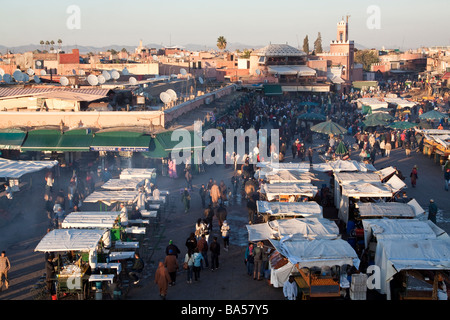 View from cafe roof terrace in the early evening dusk looking over the busy food stalls of the place Jemaa el Fna, - Stock Photo
