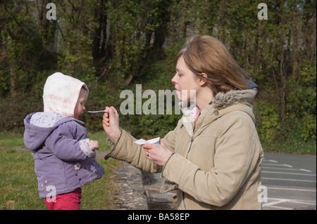 Wales - mother feeding one year old girl toddler, out walking - Stock Photo
