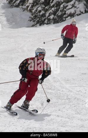 Skiers descend a groomed run, Aspen Highlands Ski Area, Aspen, Colorado. - Stock Photo