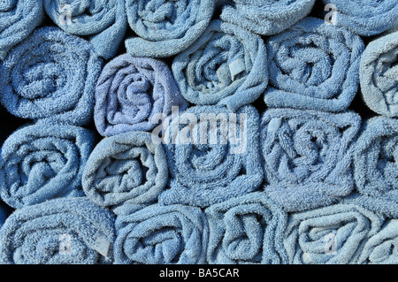 Abstract background end view close up of blue rolled up towel in stacks beside pool awaiting use by cruise ship - Stock Photo