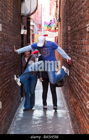 Man performing a split between the walls of a narrow street Fan Tan Alley in Chinatown Victoria BC Canada - Stock Photo