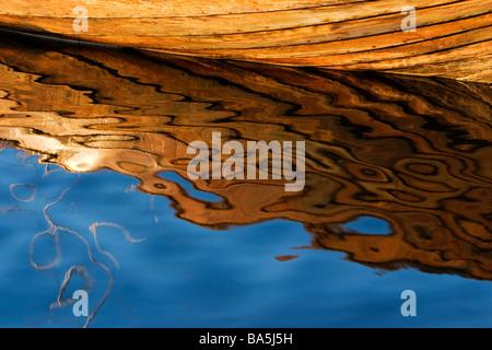 Wooden oar boat reflected in water. - Stock Photo