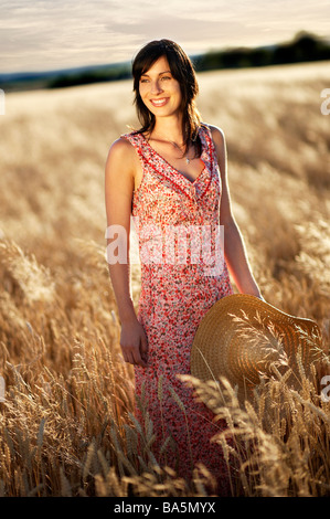 Beautiful Woman Standing in the Field, holding Hut - Stock Photo