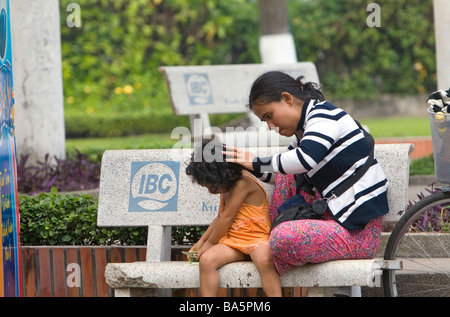 Vietnamese woman checking her childs hair for lice in Ho Chi Minh City Vietnam - Stock Photo