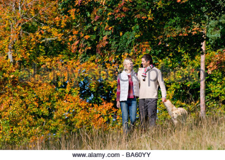 Couple walking through field with dog - Stock Photo