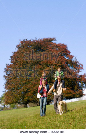 Family and dog walking through field - Stock Photo