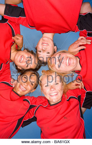 Portrait of smiling teenage girls hugging in sports uniforms - Stock Photo