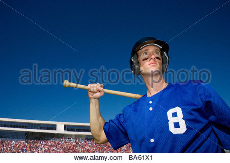 Baseball player holding bat with crowd in background - Stock Photo