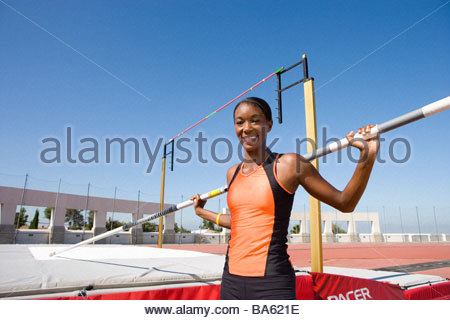 Young female pole vault athlete with pole by bar, smiling, portrait - Stock Photo