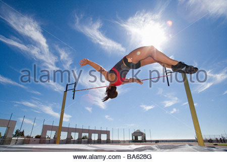 Female athlete jumping over bar, low angle view (lens flare) - Stock Photo