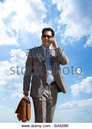 Businessman talking on cell phone with background of clouds in blue sky - Stock Photo