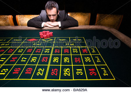Man with pile of chips at roulette table - Stock Photo