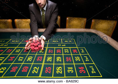 Man pushing pile of chips on roulette table - Stock Photo