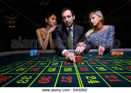 Man flanked by women, gambling at roulette table, portrait, low angle view - Stock Photo