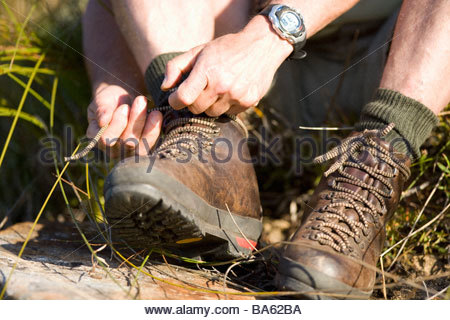 Close up of man tying hiking boots - Stock Photo