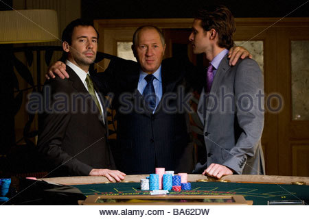 Mature man with arms around young men by poker table, portrait - Stock Photo
