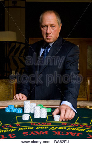 Mature man placing gambling chips on poker table, portrait - Stock Photo