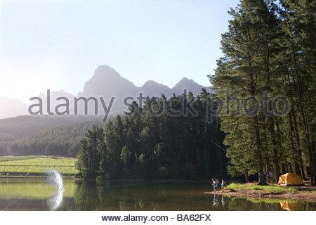 Family fishing at lakeís edge - Stock Photo