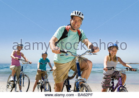 Portrait of family riding bicycles on beach - Stock Photo