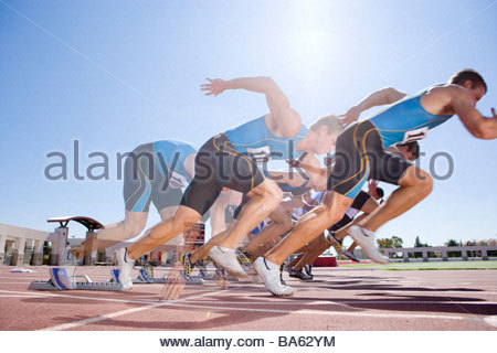 Runners emerging from starting block in multiple exposure - Stock Photo