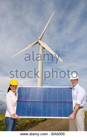 Man and woman in hard hats holding solar panel beneath wind turbine - Stock Photo