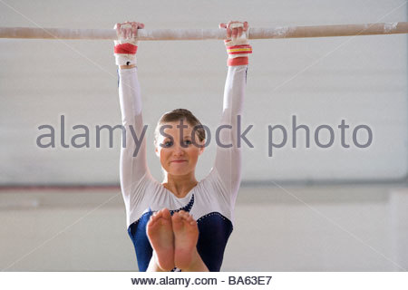 Female gymnast performing on bar, smiling, portrait - Stock Photo