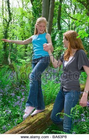 Mother and daughter playing on log among bluebell flowers - Stock Photo