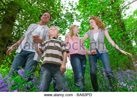 Family walking through field of bluebell flowers - Stock Photo