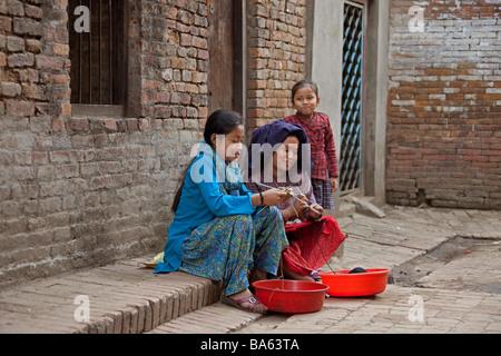 Woman and two young girls knitting, sitting on pavement in street, kathmandu nepal Horizontal  92693 Nepal-Kathmandu - Stock Photo