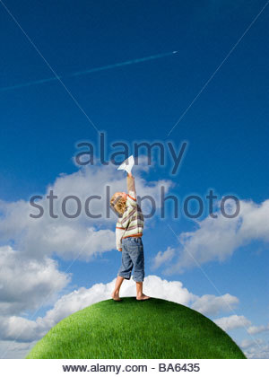 Boy throwing paper airplane on top of grassy globe - Stock Photo