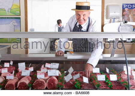 Butcher in uniform behind meat counter - Stock Photo
