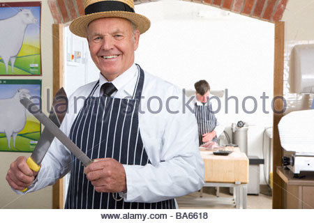 Butcher in uniform sharpening knife - Stock Photo