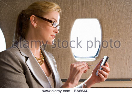 Businesswoman using electronic organiser on aeroplane, side view - Stock Photo