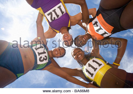 Small group of female athletes arm in arm forming circle, smiling, portrait, view from below - Stock Photo