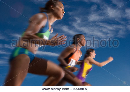 Low angle view of female athletes running in race - Stock Photo