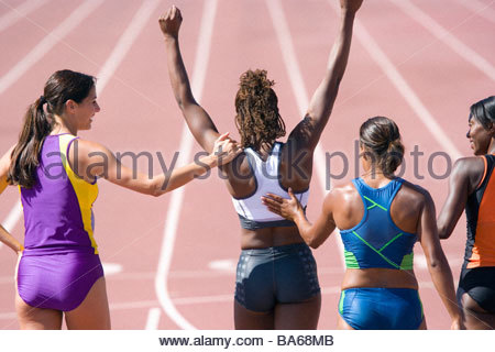 Female runner cheering victory on race track - Stock Photo