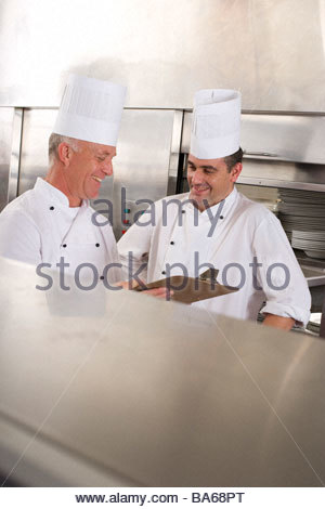 Chefs in commercial kitchen - Stock Photo