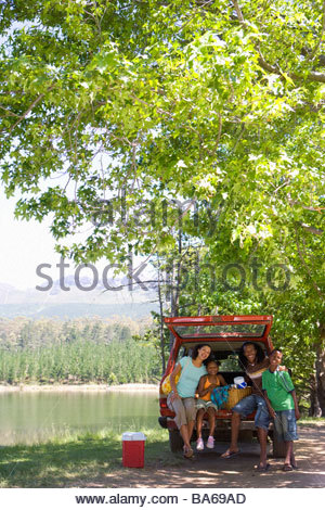 Family picnicking in car by lake - Stock Photo