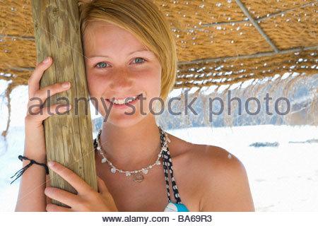 Teenage girl posing under beach umbrella - Stock Photo