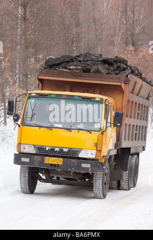 Trucks hauling low grade coal from an open cast coal mine near Heihe on the Chinese Russian border. - Stock Photo