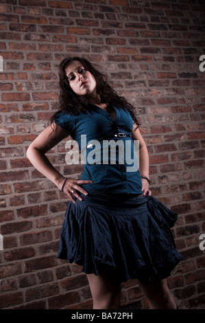Young woman standing in a dark alley at night Stock Photo