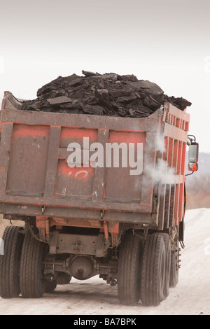 Trucks hauling low grade coal from an open cast coal mine near Heihe on the Chinese Russian border - Stock Photo