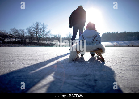Father pulling sledge with child on frozen lake Buchsee, Munsing, Bavaria, Germany - Stock Photo