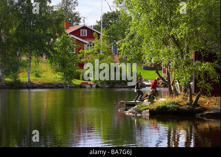 House and children, playing at the bank in Sundborn, Dalarna, middle Sweden - Stock Photo